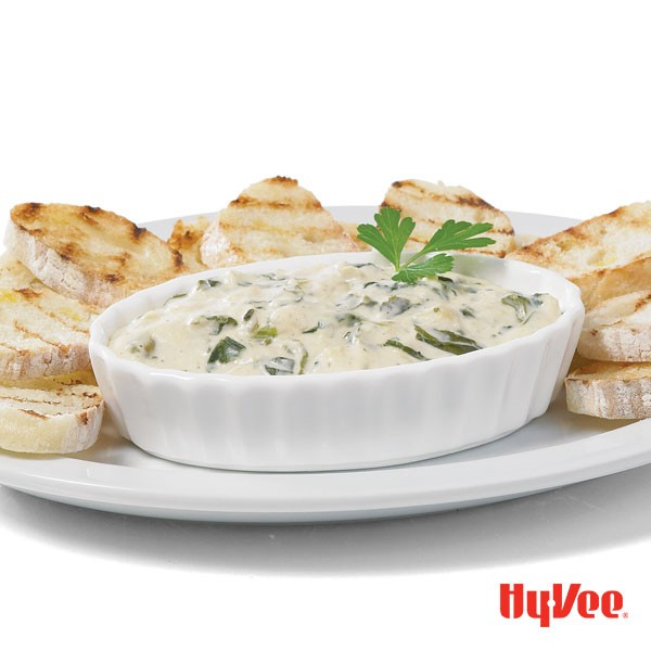 Bowl of spinach and artichoke dip, served with plate of bread