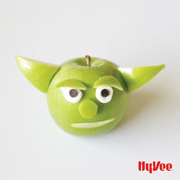 Green apple with cut apples for ears, eyebrows nose and mouth with marshmallow and mini chocolate chip eyes