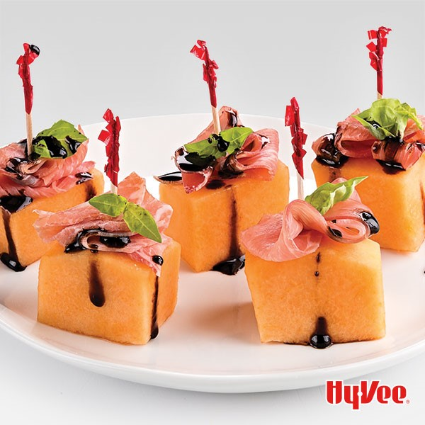 White plate of cantaloupe cubes topped with prosciutto, basil and balsamic and held together with a toothpick