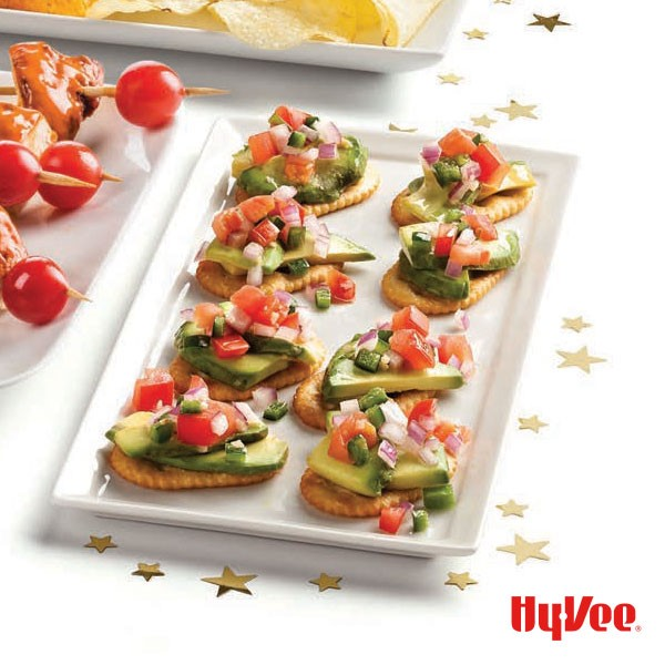 Platter of crackers topped with sliced avocado, pico de gallo and red pepper flakes