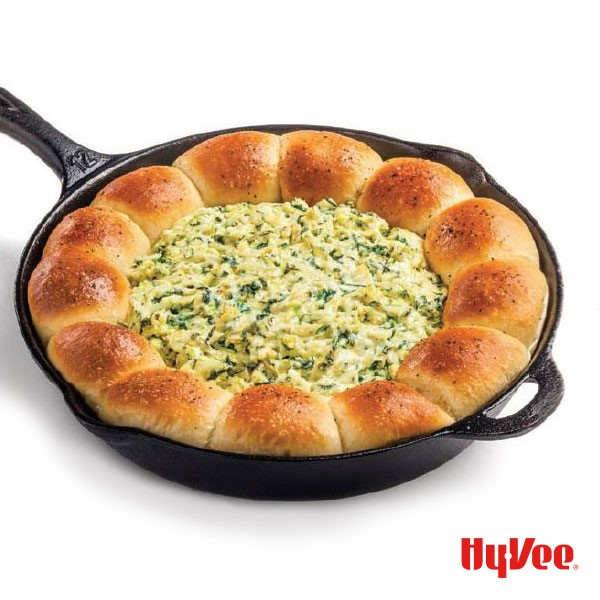 Cast-iron skillet with bread along the inside ring filled with spinach and artichoke dip