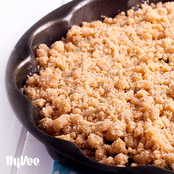 Black scalloped ban filled with cranberry apple pie and garnished with a crumb topping