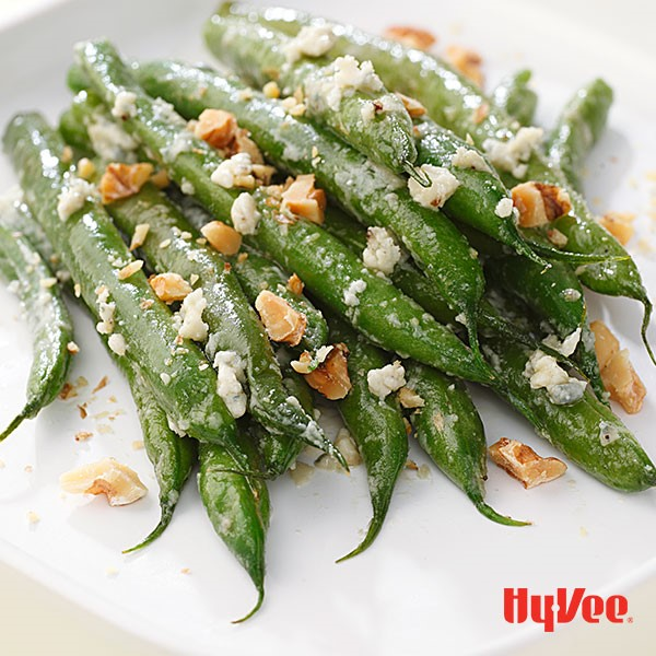 Platter of green beans topped with blue cheese and chopped walnuts