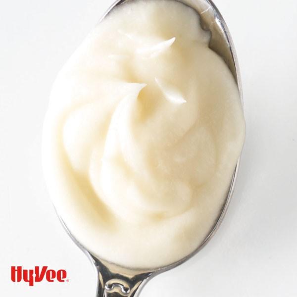 Fluffy vanilla butter cream in metal spoon