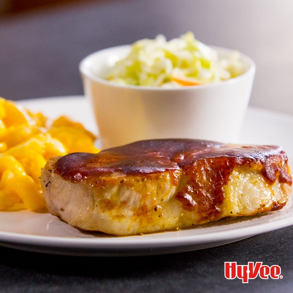 Pork chop topped with barbecue sauce with a side of coleslaw and mac and cheese