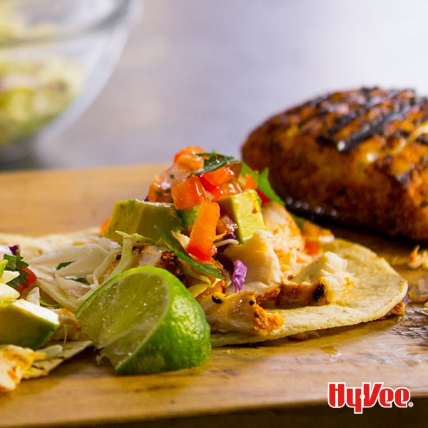 Corn tortillas topped with shredded white fish, diced avocados and tomatoes, and with a side of lime wedges