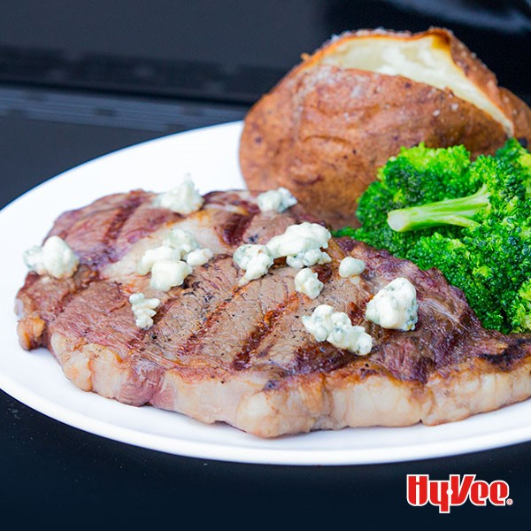 White plate topped with grilled rib eye steak and crumbled blue cheese with a side of broccoli and baked potato