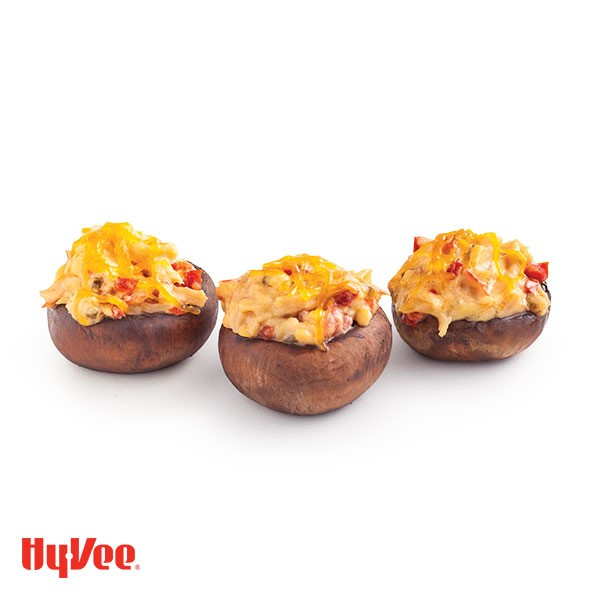 Three whole mushrooms stuffed with melted cheese and peppers