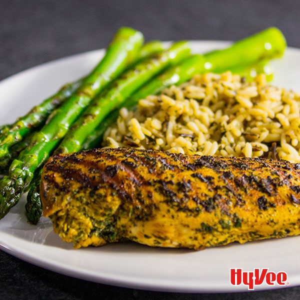 Grilled chicken breast on white plate with sides of grilled asparagus spears and rice