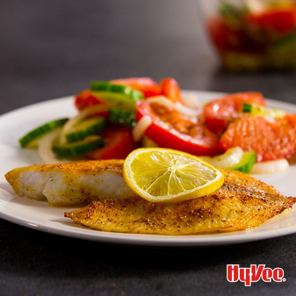 Baked seasoned tilapia garnished with a lemon slice with a side of tomatoes and cucumbers