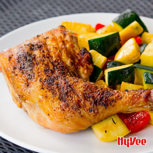 Grilled lemon chicken leg quarter with a mixed medly of chopped summer squash, zucchini, and red bell pepper