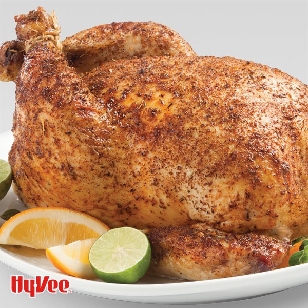 A whole chicken roasted in a citrus-and-herb rub and served with orange and lime wedges