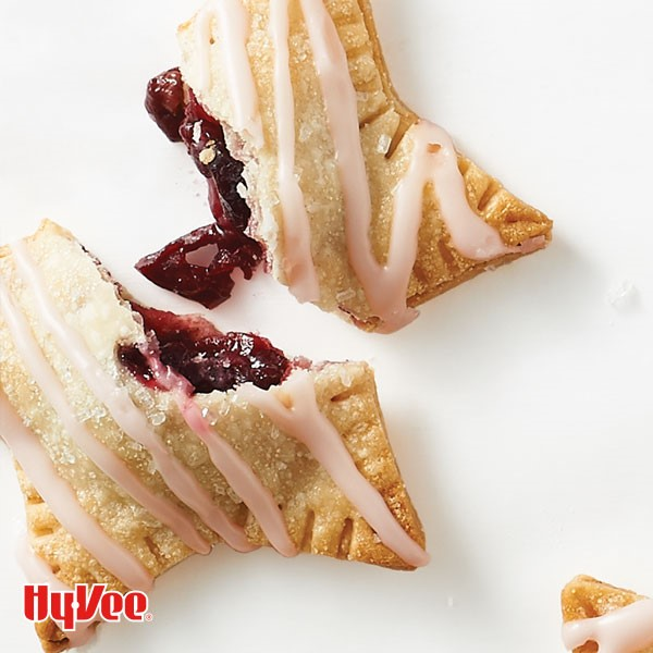 Mini cherry pies drizzled in a cherry juice glaze and sprinkled with coarse sugar