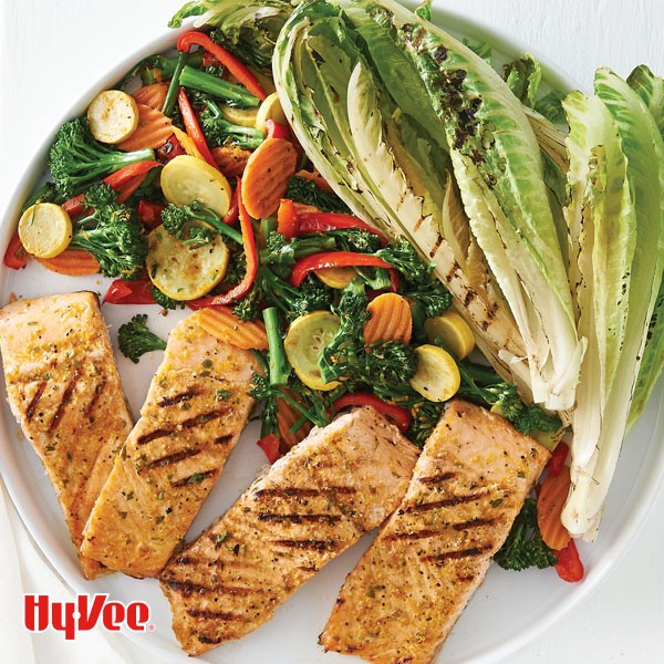 Grilled romaine and 4 pieces of salmon with diced carrots, broccoli florets, summer squash and sliced red peppers on white plate