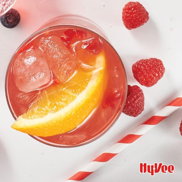 Red raspberry tea drink with ice cubes, orange wedge, and raspberries