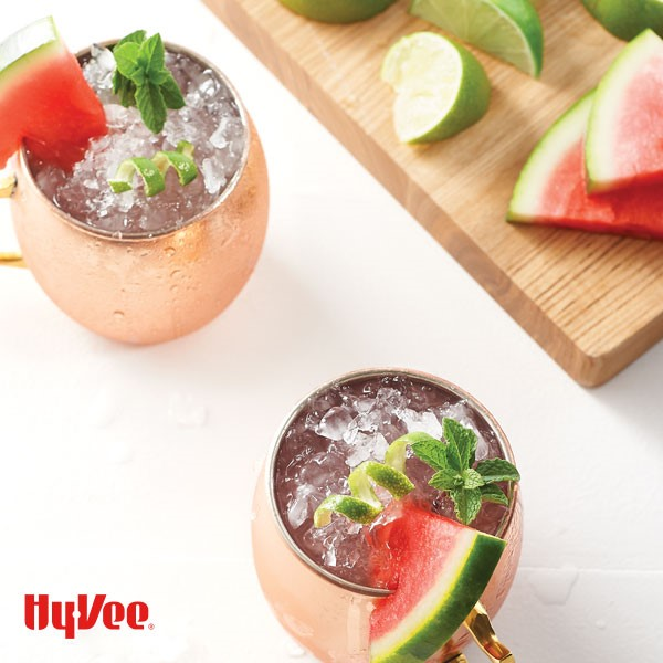 Copper cups topped with crushed ice, basil leaves, lime peel, and watermelon slice