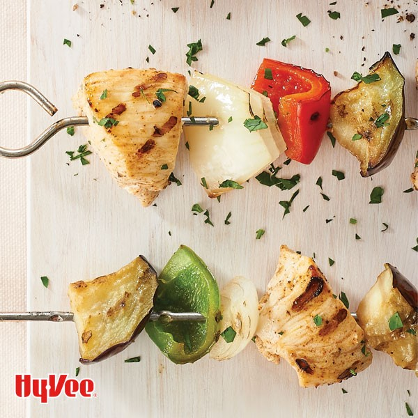 Metal skewers with pieces of grilled chicken, white  onion, red bell pepper, and eggplant