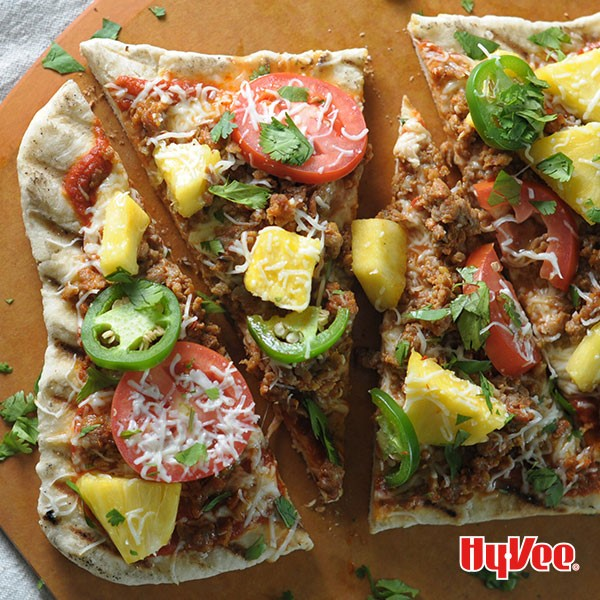 Thin grilled pizza crust topped with ground meat, jalapenos, pineapple chunks, sliced tomatoes, and shredded cheese