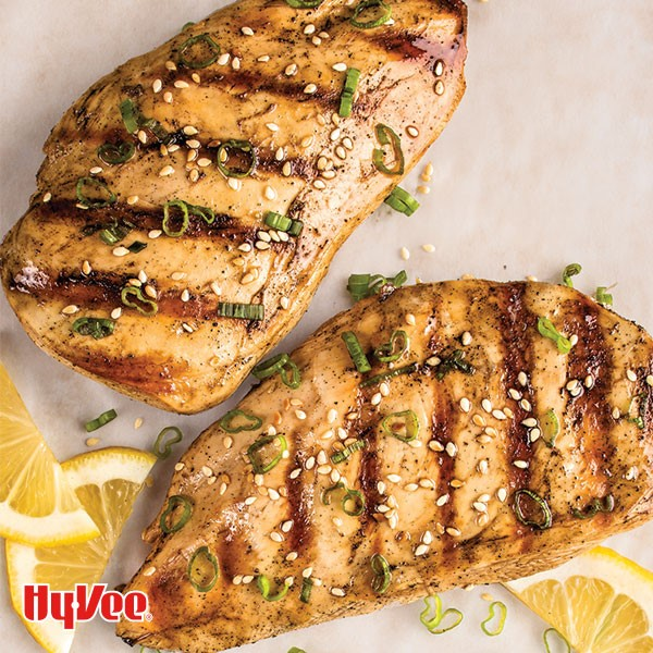 Grilled chicken breasts topped with sesame seeds, sliced green onions, and lemon wedges