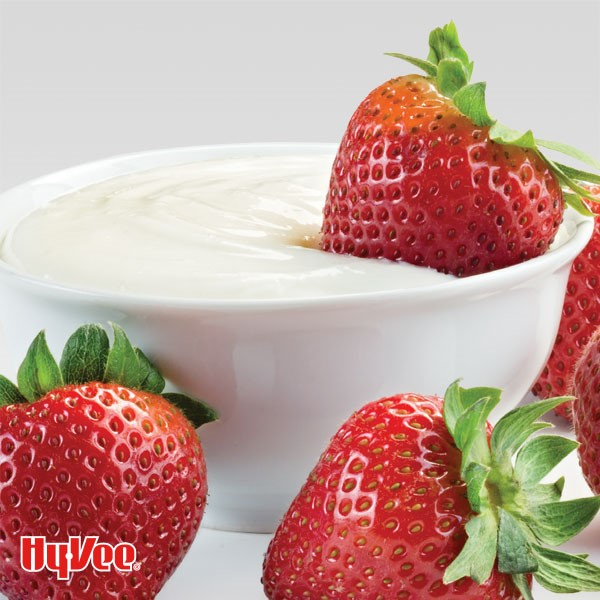 White fruit dip in a serving bowl with whole strawberries on the side