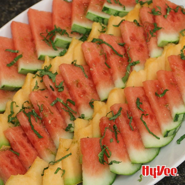 Watermelon and cantaloupe slices topped with thin slices of basil on a white serving platter