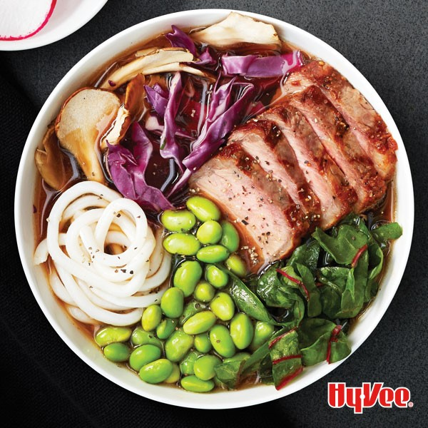 Bowl filled with noodles, edamame beans, red cabbage and sliced steak