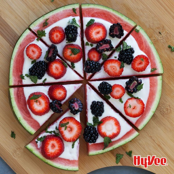 Sliced watermelon topped with sliced strawberries, black berries, and chopped mint