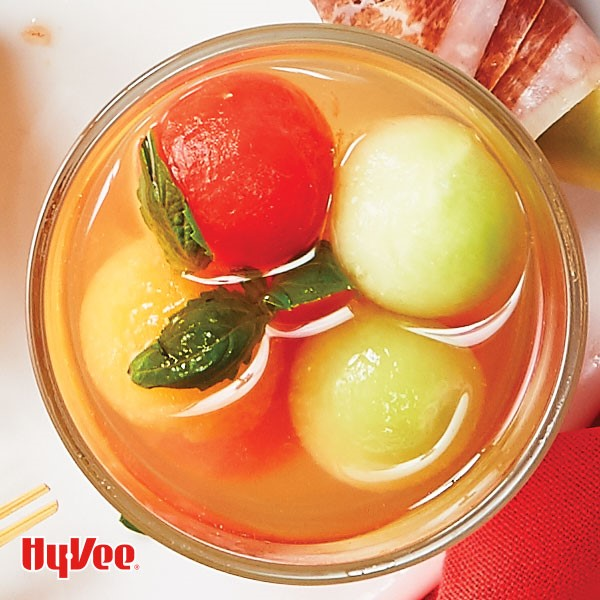 Glass filled with assorted melon balls and garnished with fresh basil leaves