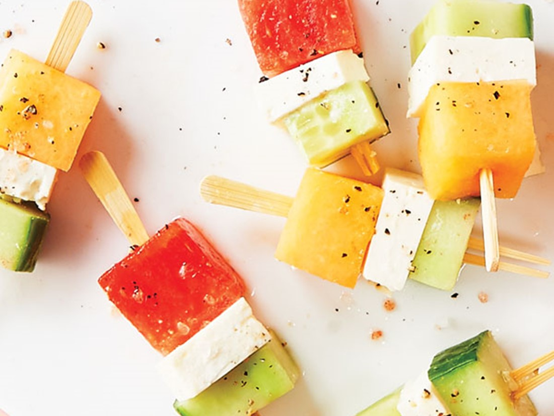 Square cut cucumbers, cheese, and melon on wooden sticks and sprinkled with salt and ground black pepper