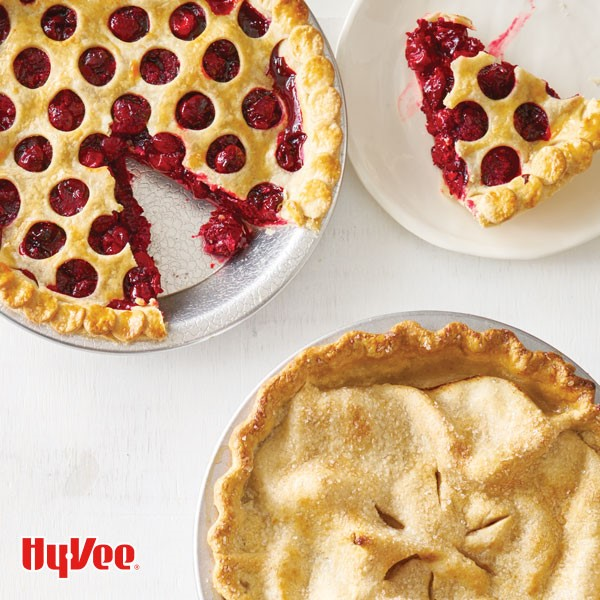 Cherry pie with circles cut out of top crust and a wedge on a plate next to double crusted pie with fluted crust