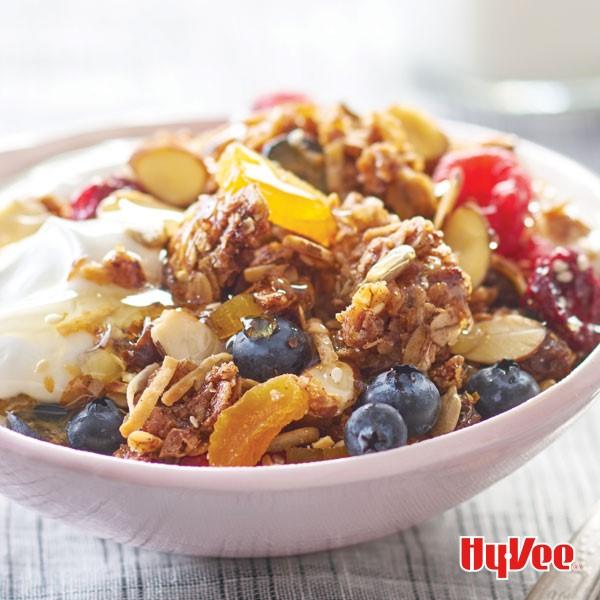 Bowl of almond granola topped with yogurt, honey and fresh fruit