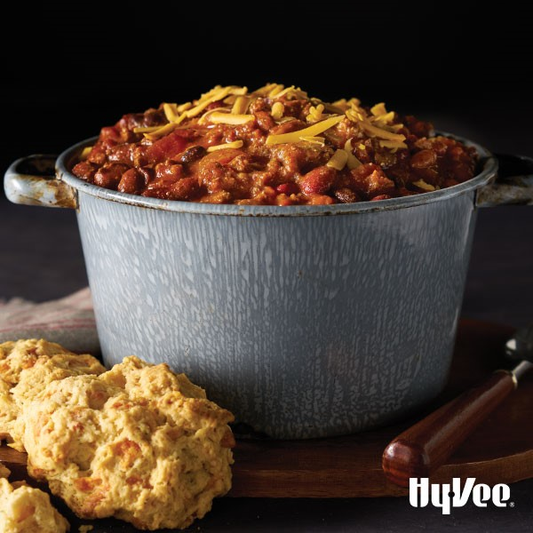 Chili in a bowl with shredded yellow cheese and a side of biscuits