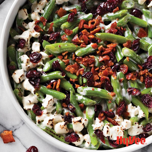 Dish of green bean casserole filled with goat cheese, dried cranberries and bacon bits