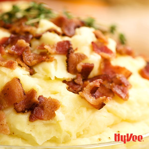 Mashed potatoes topped with cooked chopped bacon with fresh thyme sprigs