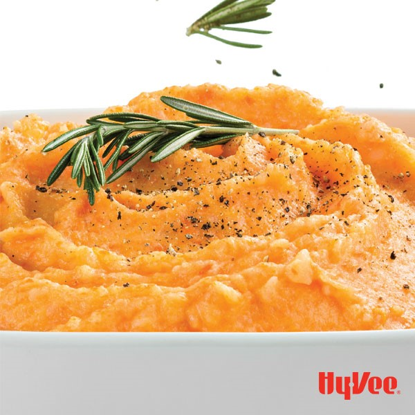 Orange vegetable mash in a casserole dish topped with black pepper and fresh rosemary sprigs