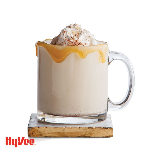 Caramel-rimmed glass of egg nog, garnished with whipped cream and a sprinkle of pumpkin pie spice