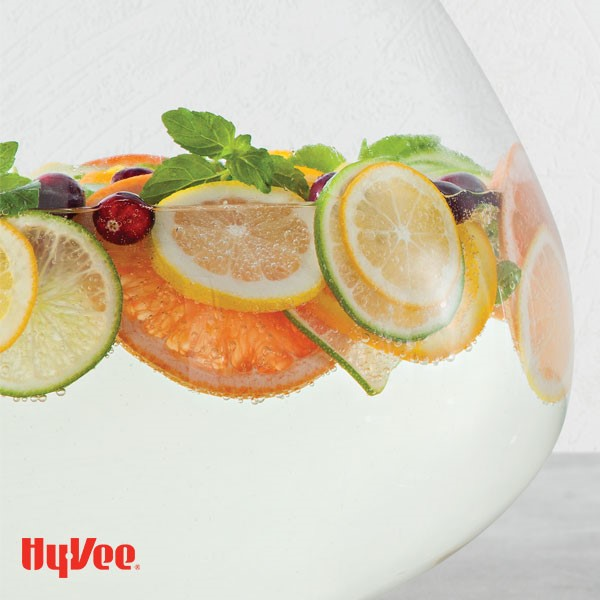 Spritzer filled bowl with sliced citrus, mint leaves and whole cranberries