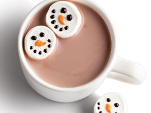 Mug of hot chocolate served with snowman-decorated marshmallows using chocolate and orange melts