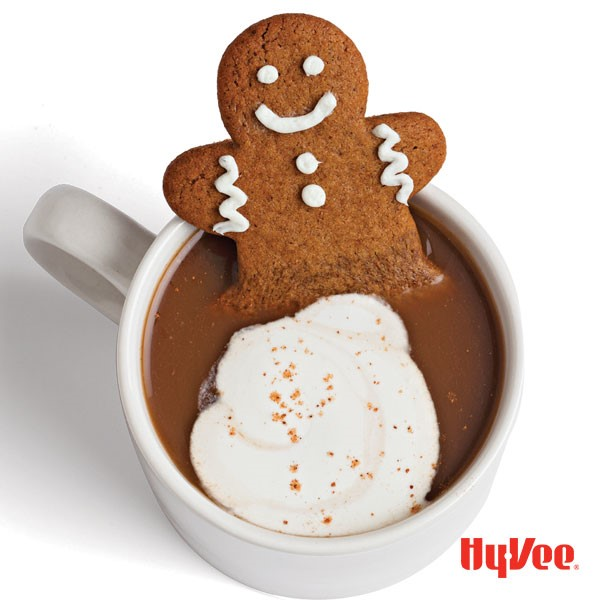 White mug filled with gingerbread latte, whipped topping, and a decorated gingerbread man