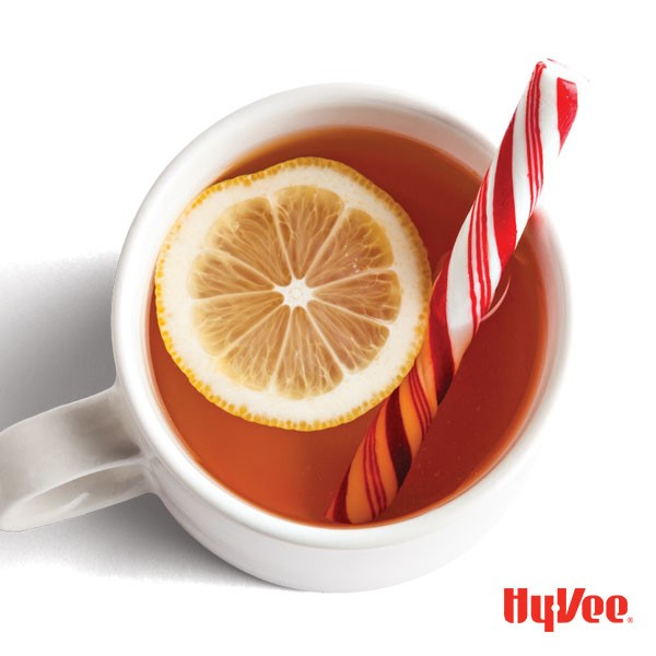 Mug of hot toddy, garnished with lemon slice and peppermint candy stick