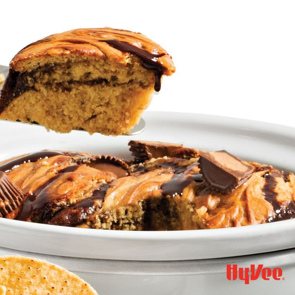 Peanut butter cake topped with chocolate syrup and Reese's mini peanut butter cups in a slow-cooker