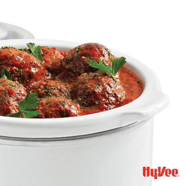 Slow cooker filled with meatballs and red sauce and garnished with fresh Italian parsley