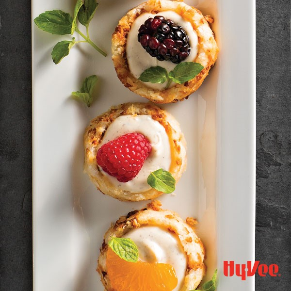 Platter of macaroons filled with vanilla creme fraiche and garnished with fruit and mint leaves