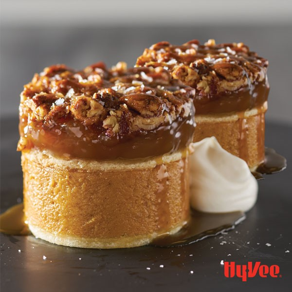 Round of pumpkin pie topped with pecan pie filling with nuts on top, drizzled in syrup with dollop of whipped cream on side