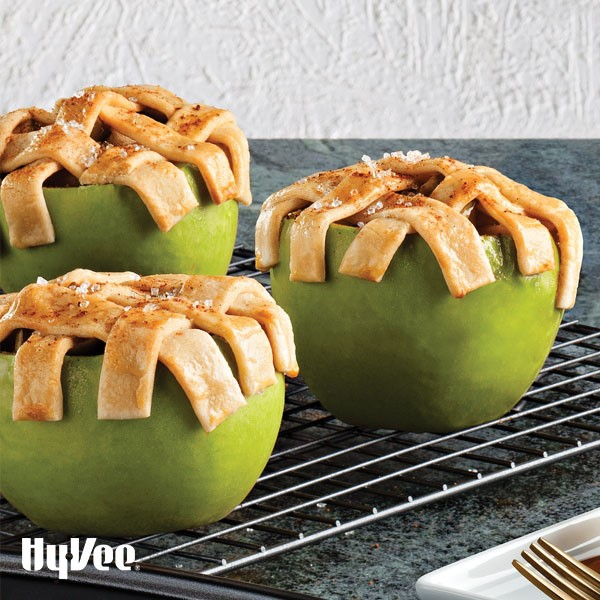 Green apples topped with a lattice pie crust on a cooling rack
