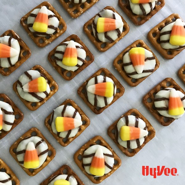 Waffle pretzels topped with Hershey's hugs and candy corn on parchment paper