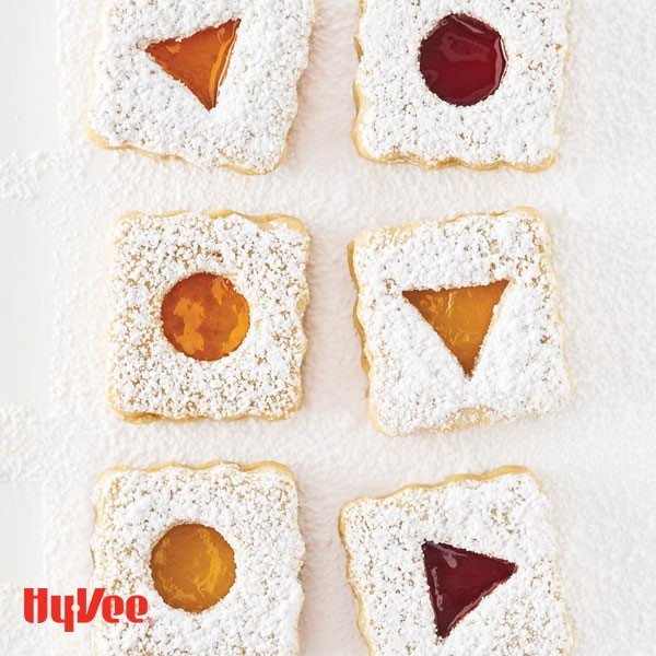 Almond cookies with fruit preserve filling coated in powdered sugar on parchment paper
