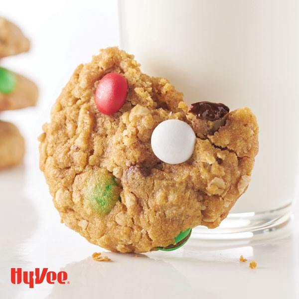 Monster cookie with piece missing leaning against glass of milk and filled with red, green, and white candy coated chocolate pieces.