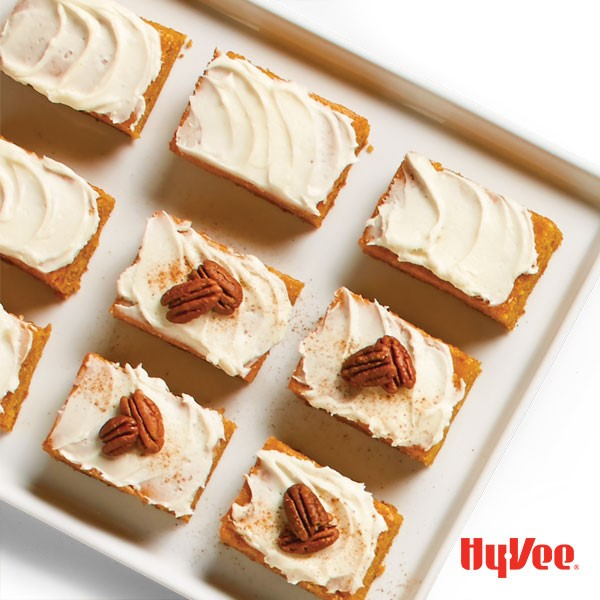 Pumpkin bars, cut on a white platter topped with cream cheese frosting, two pecan halves each, and a sprinkle of cinnamon