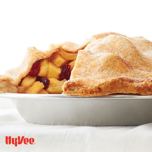 Pie plate filled with cranberry and apple filling and topped with flaky-sugar crusted pie crust